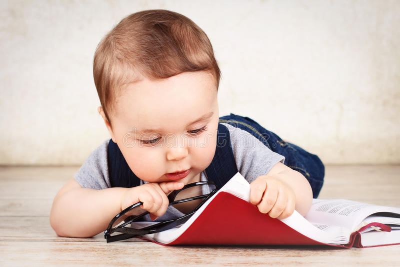 Petit bébé garçon avec les verres et le livre image libre de droits