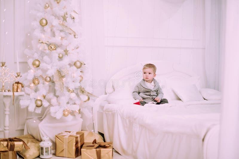 Petit bébé garçon gai jouant près de l'arbre de Noël, de l'or et du pastel beige c image stock
