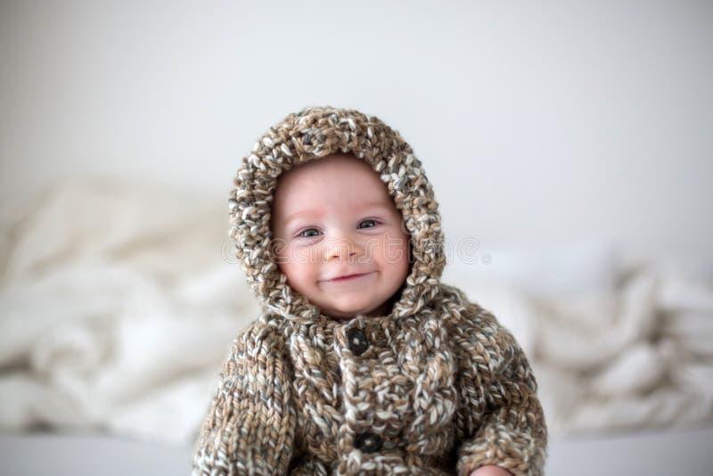 Petit bébé garçon jouant à la maison dans le lit, habillé dans le kni fabriqué à la main photos libres de droits