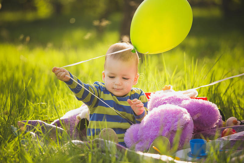 Petit bébé garçon jouant des jouets se reposant sur la longue herbe verte dehors images libres de droits