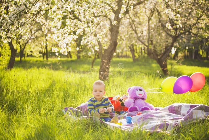 Petit bébé garçon jouant des jouets se reposant sur la longue herbe verte dehors photos stock