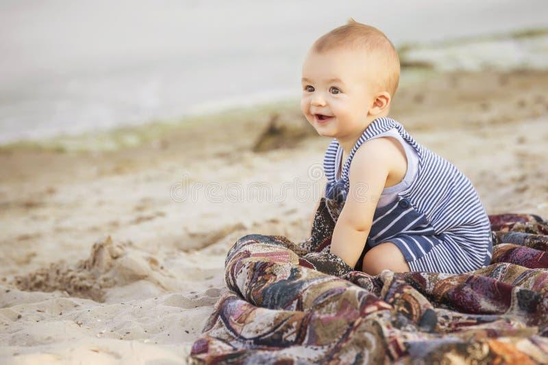 Petit bébé infantile mignon de sourire heureux sur un bord de la mer près de l'eau i photographie stock libre de droits