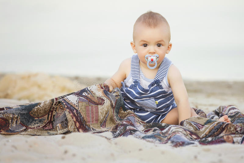 Petit bébé infantile mignon de sourire heureux sur un bord de la mer près de l'eau i photos stock