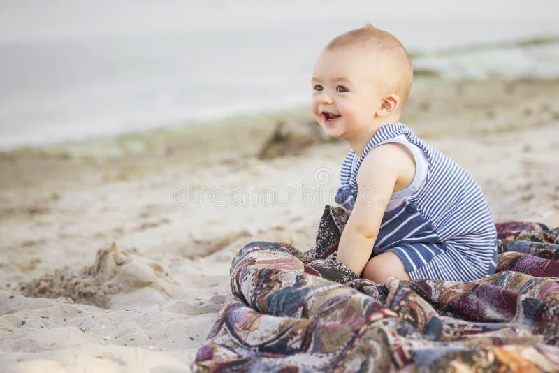 Petit bébé infantile mignon de sourire heureux sur un bord de la mer près de l'eau i images stock