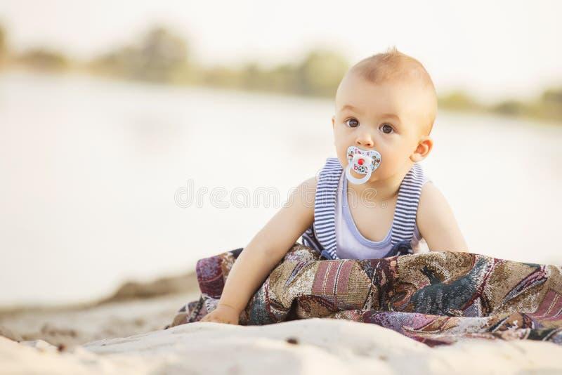 Petit bébé infantile mignon de sourire heureux sur un bord de la mer près de l'eau i photos libres de droits