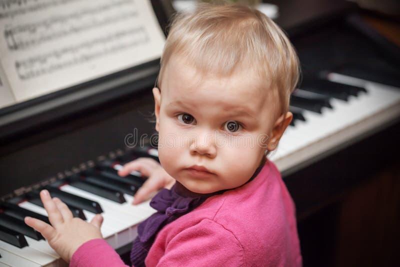 Petit bébé jouant la musique sur le piano images stock