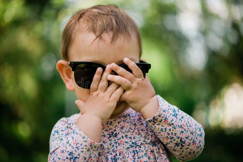 Petit bébé jouant le visage de dissimulation de fille de BO-piaulement Fond d'?t? sunglasses image stock
