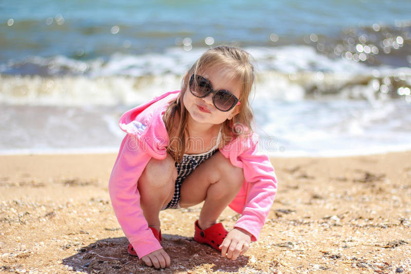Petit bébé jouant sur la plage de sable photo stock