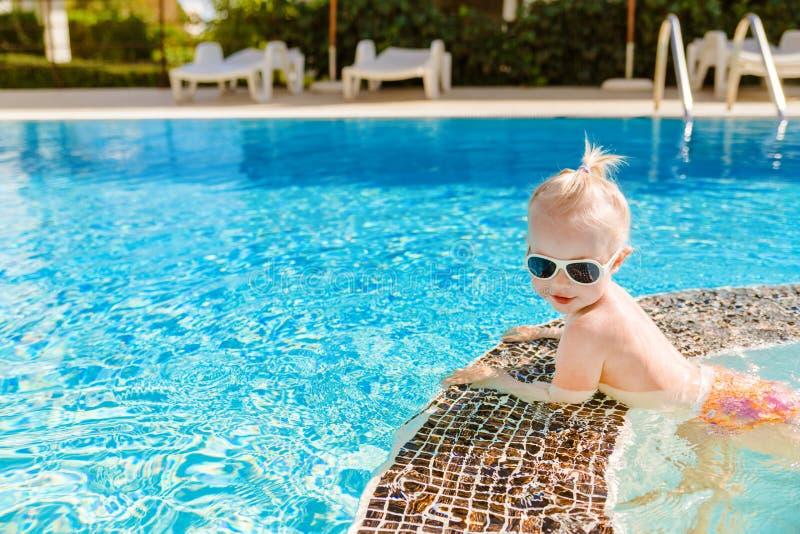 Petit bébé mignon avec des lunettes de soleil nageant dans la piscine photo libre de droits