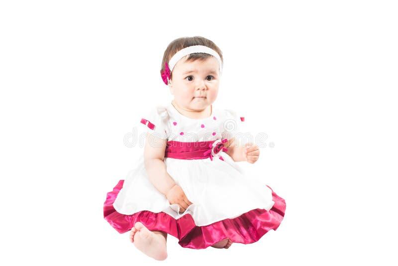 Petit bébé mignon dans la robe rose d'isolement sur le fond blanc images stock