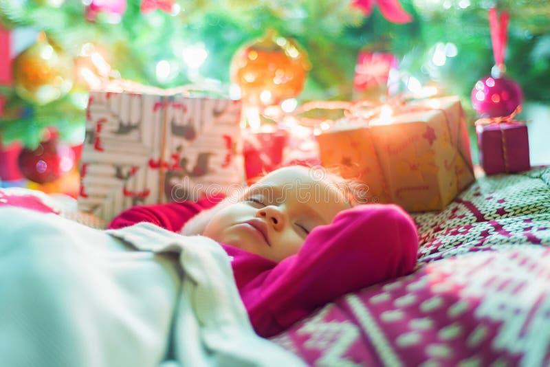 Petit bébé mignon dormant près de l'arbre de Noël images libres de droits