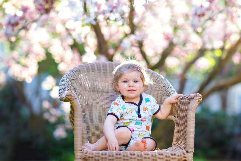 Petit bébé mignon s'asseyant sur la grande chaise dans le jardin Bel enfant en bas âge de sourire heureux avec l'arbre rose de fl photo libre de droits