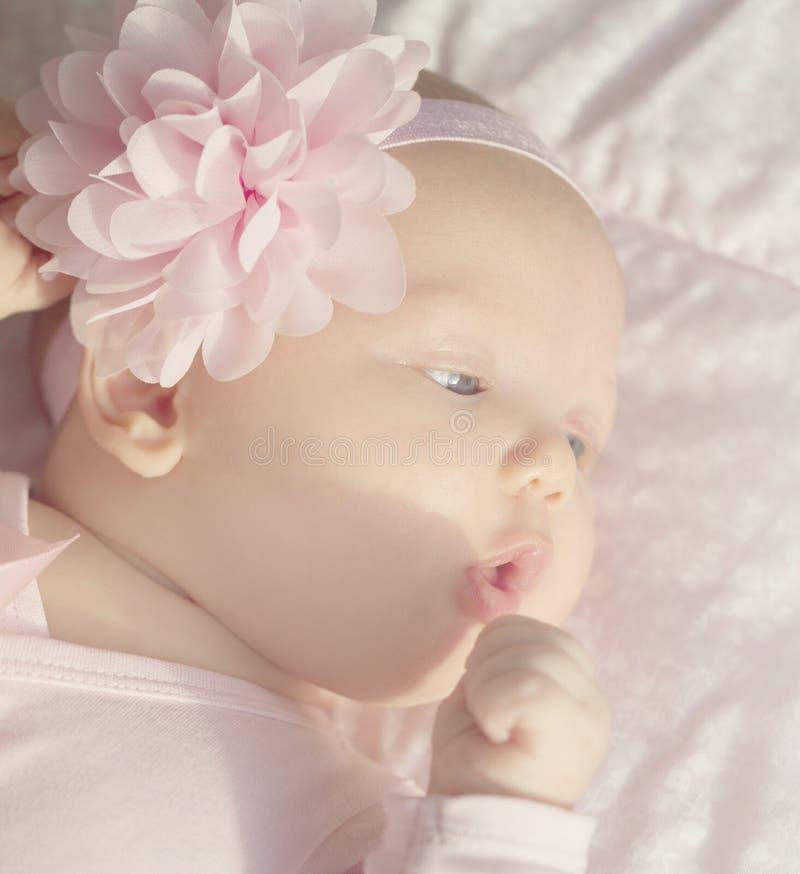 Petit bébé mignon se situant dans son lit, le tenant main sur la bouche photo stock
