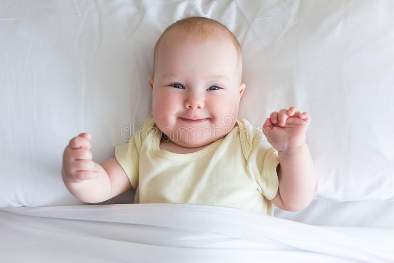 Petit bébé mignon se trouvant sur le lit sous la couverture photo stock