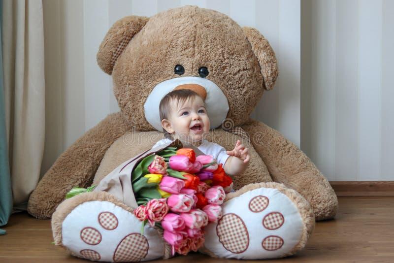 Petit bébé mignon souriant avec ses premières dents, se reposant sur l'ours de nounours énorme avec le grand bouquet des tulipes photos stock