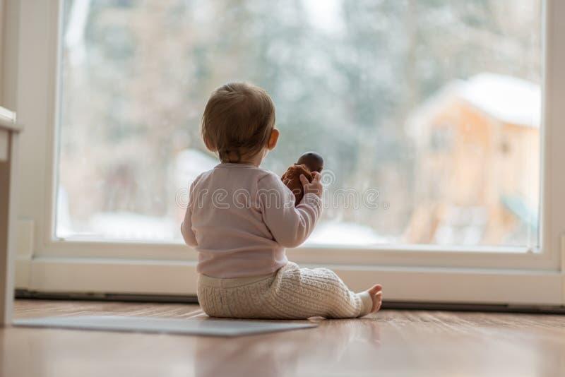 Petit bébé observant la neige dehors image libre de droits
