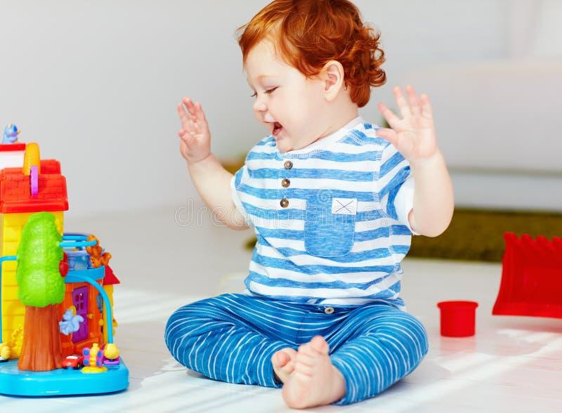 Petit bébé roux heureux jouant avec la maison de jouet images stock