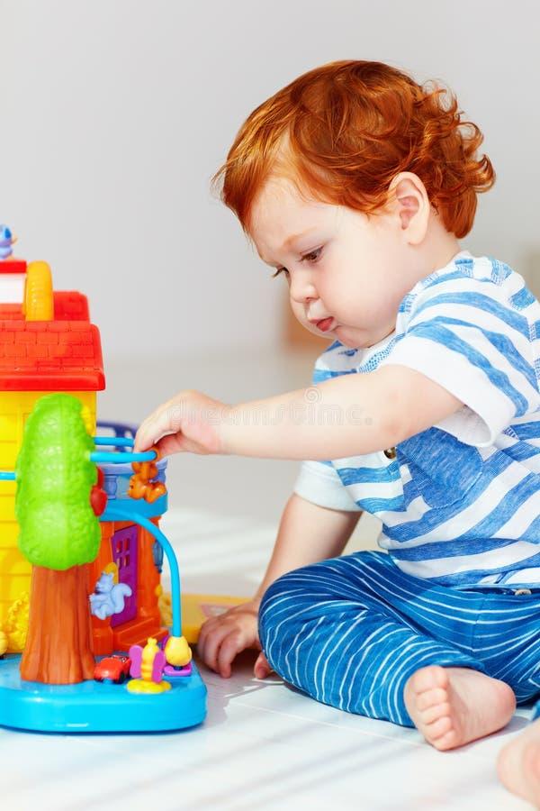 Petit bébé roux mignon jouant avec la maison de jouet photos libres de droits