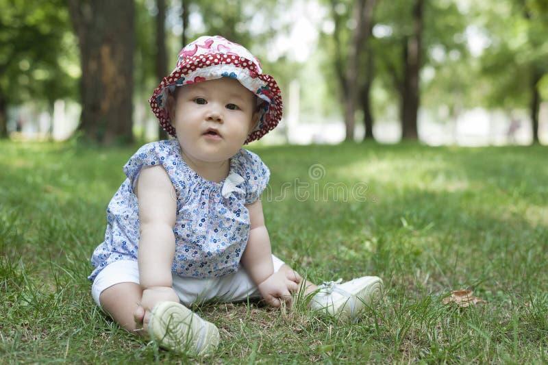 Petit bébé s'asseyant sur l'herbe photo libre de droits