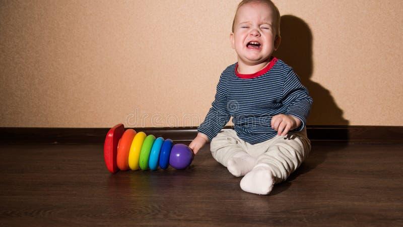 Petit bébé s'asseyant sur le plancher et pleurer images stock