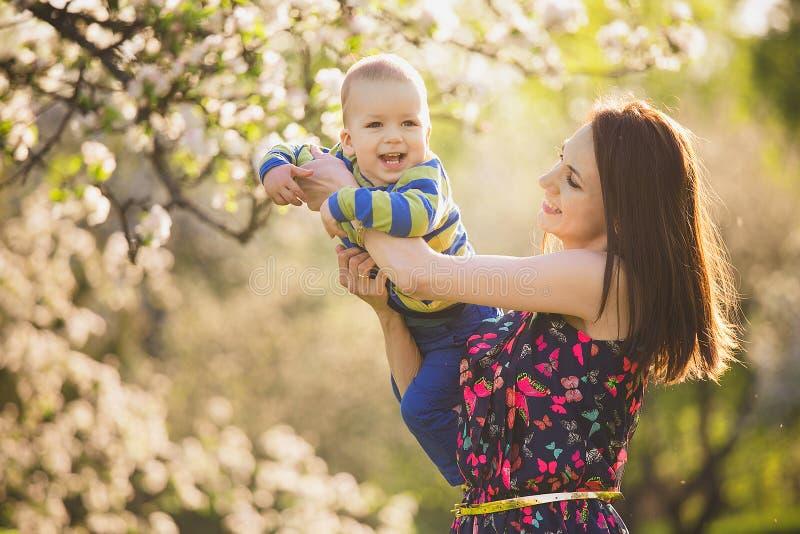 Petit bébé sur des mains de mère femme jouant avec l'enfant dehors photographie stock