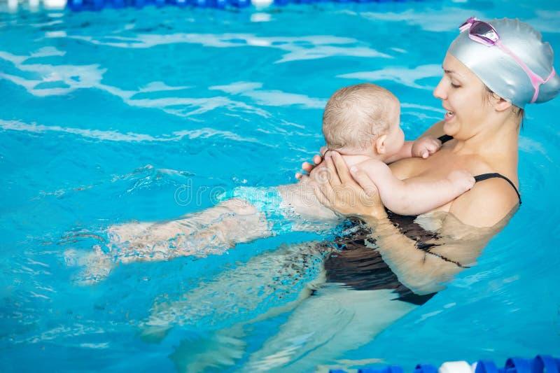 Petit bain d'enfant avec sa mère dans la piscine photographie stock libre de droits