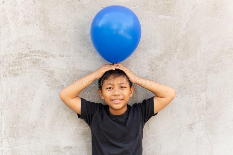 Petit ballon asiatique de participation de garçon sur sa tête avec le fond gris photo libre de droits