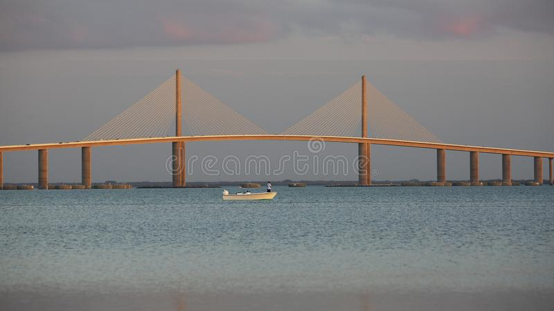 Petit bateau de pêche sous le pont de Skyway de soleil - la Floride photographie stock