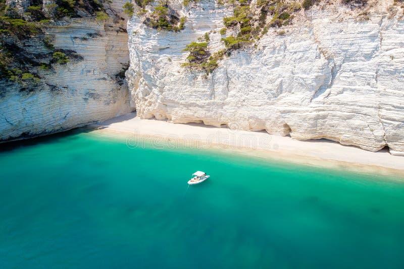 Petit bateau de récréation dans le beau golfe avec de l'eau turquoise Piles de mer de Faraglioni en Puglia, delle Zagare de Baia images stock