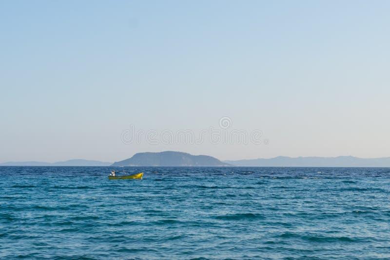 Petit bateau motorisé jaune avec des voiles d'un homme en mer ouverte photos libres de droits