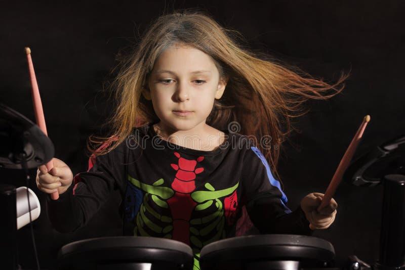 Petit batteur caucasien de fille avec les cheveux multicolores jouant le kit électronique de tambour photographie stock