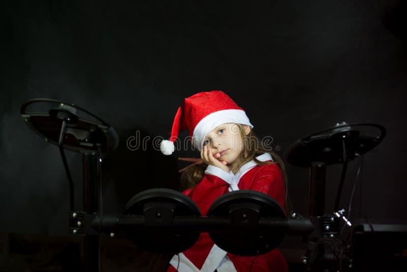 Petit batteur déguisé comme Santa Claus jouant le kit elettronic de tambour images libres de droits