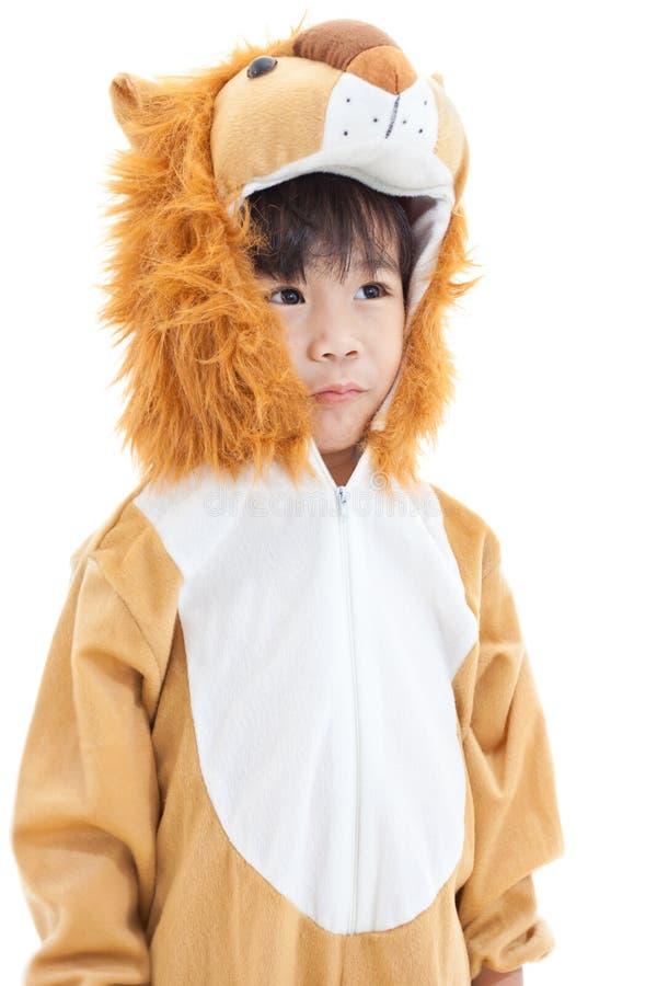 Petit beau garçon asiatique costumé comme un lion et penser à l'avenir photo libre de droits