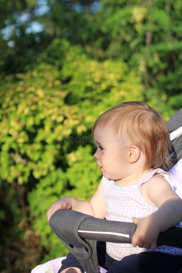 petit, beau, souriant, bébé roux mignon dans des -de-portes d'un landau dans penser à l'avenir sans manche de chemise photo libre de droits