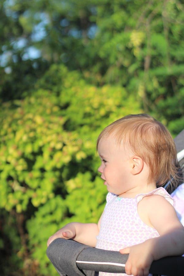 petit, beau, souriant, bébé roux mignon dans des -de-portes d'un landau dans penser à l'avenir sans manche de chemise image stock
