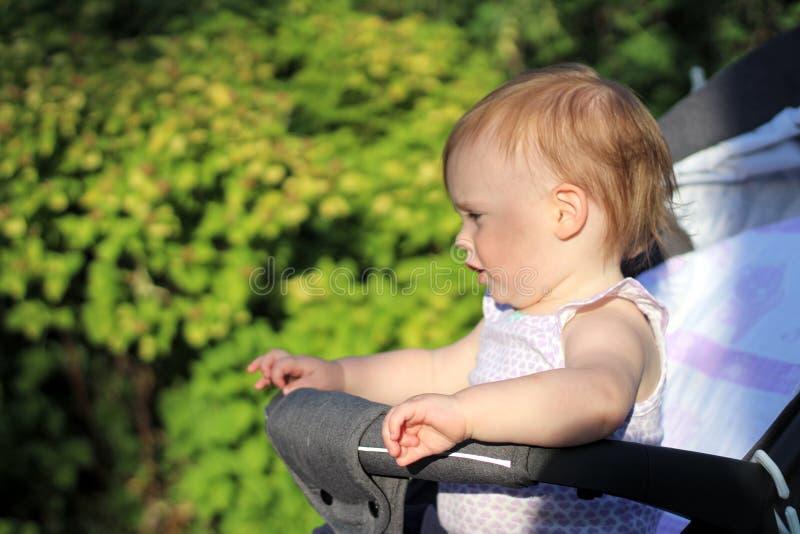 petit, beau, souriant, bébé roux mignon dans des -de-portes d'un landau dans penser à l'avenir sans manche de chemise photos libres de droits