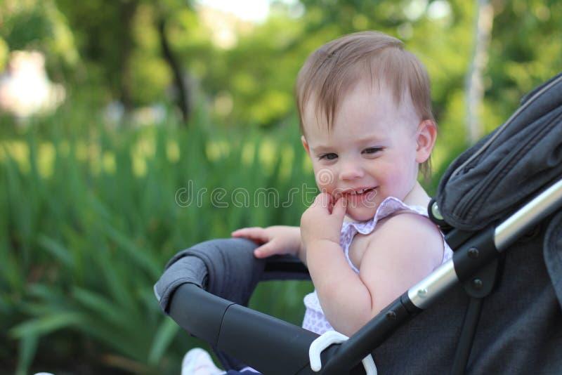 petit, beau, souriant, bébé roux mignon dans des -de-portes d'un landau dans une chemise sans manche regardant vers le bas images stock
