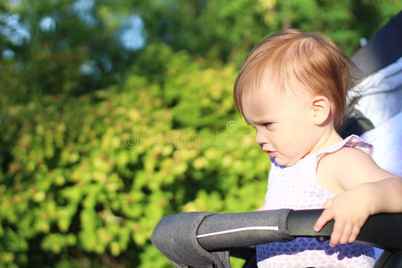 petit, beau, souriant, bébé roux mignon dans des -de-portes d'un landau dans une chemise sans manche regardant vers le bas photographie stock