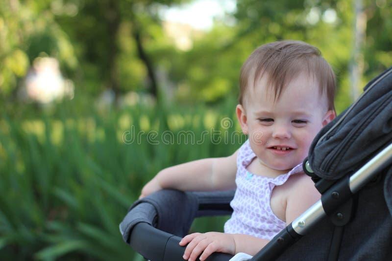 petit, beau, souriant, bébé roux mignon dans des -de-portes d'un landau dans une chemise sans manche regardant vers le bas photo libre de droits