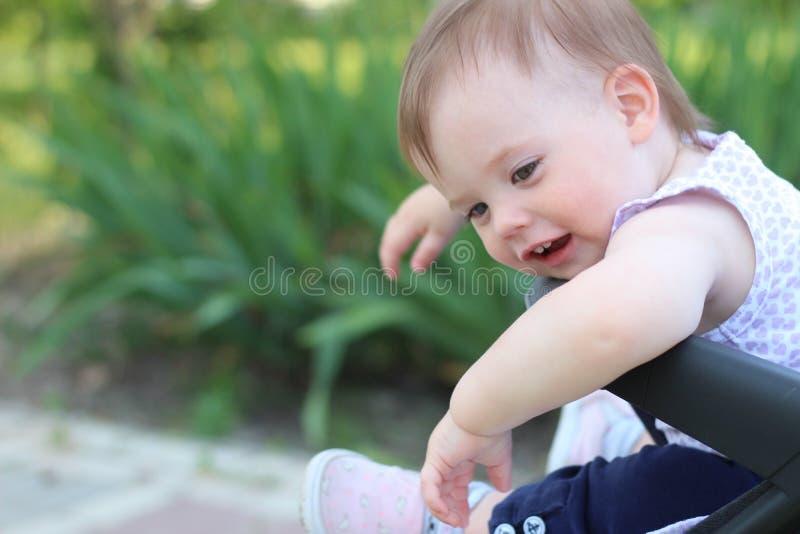 petit, beau, souriant, bébé roux mignon dans des -de-portes d'un landau dans une chemise sans manche regardant vers le bas image libre de droits
