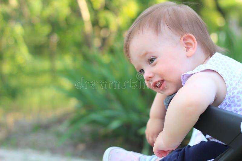 petit, beau, souriant, bébé roux mignon dans des -de-portes d'un landau dans une chemise sans manche regardant vers le bas photos libres de droits