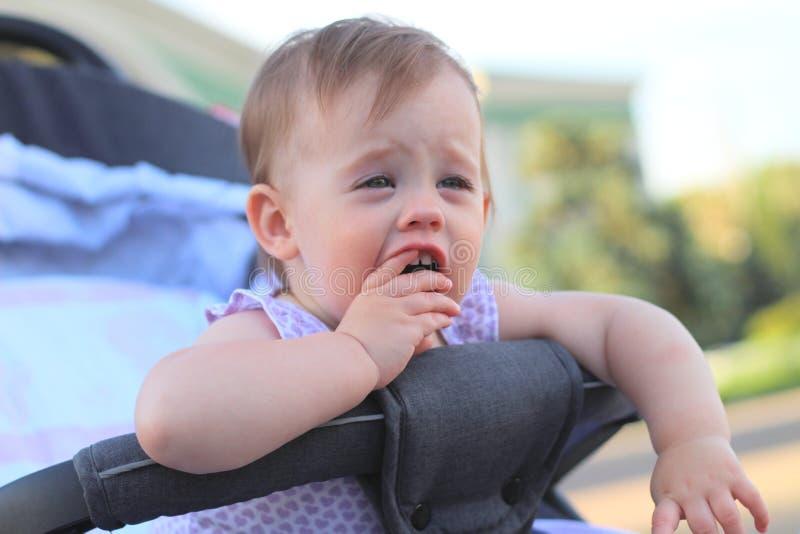 petit, beau, souriant, bébé roux mignon dans des -de-portes d'un landau dans une chemise sans manche tenant des doigts dans sa bo photographie stock libre de droits