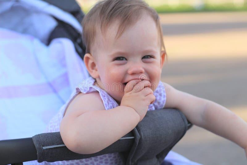 petit, beau, souriant, bébé roux mignon dans des -de-portes d'un landau dans une chemise sans manche tenant des doigts dans sa bo photos libres de droits