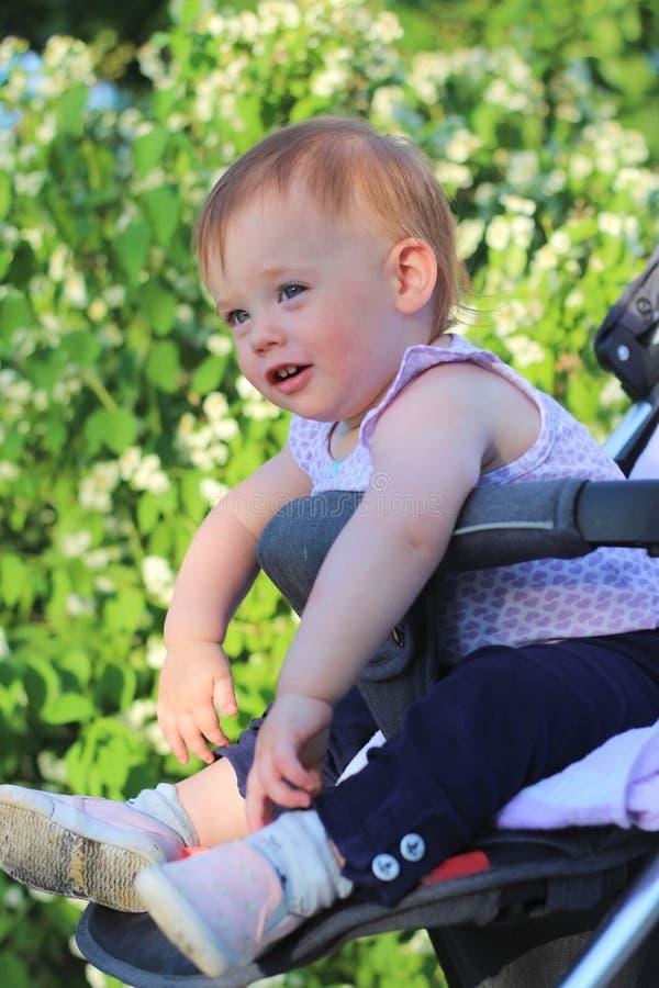 petit, beau, souriant, le bébé roux mignon dans une chemise sans manche dans des -de-portes d'un landau laisse tomber des mains v photo stock