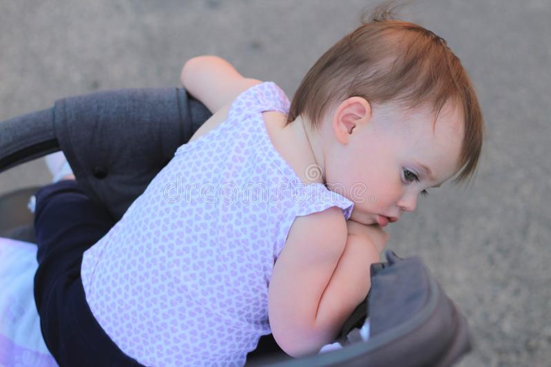 petit, beau, souriant, le bébé roux mignon dans une chemise sans manche dans des -de-portes d'un landau laisse tomber des mains v photos stock