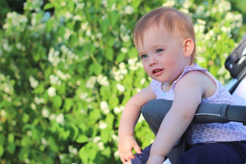 petit, beau, souriant, le bébé roux mignon dans une chemise sans manche dans des -de-portes d'un landau laisse tomber des mains v image libre de droits