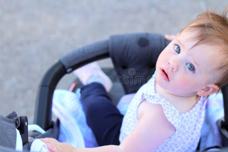 petit, beau, souriant, le bébé roux mignon dans une chemise sans manche dans des -de-portes d'un landau laisse tomber des mains v images stock