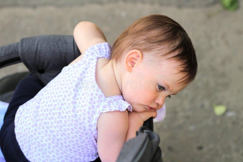 petit, beau, souriant, le bébé roux mignon dans une chemise sans manche dans des -de-portes d'un landau laisse tomber des mains v photographie stock