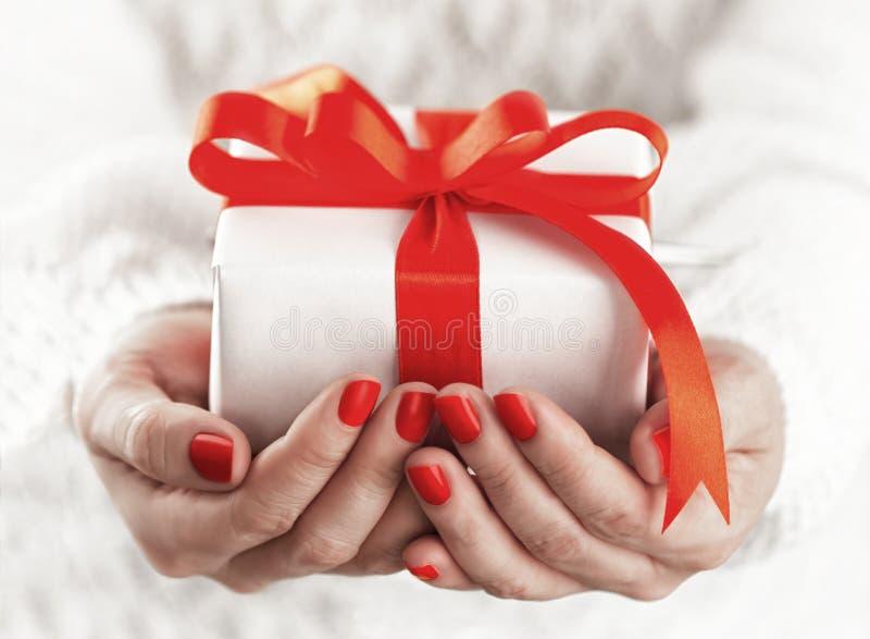 Petit boîte-cadeau dans des mains image stock