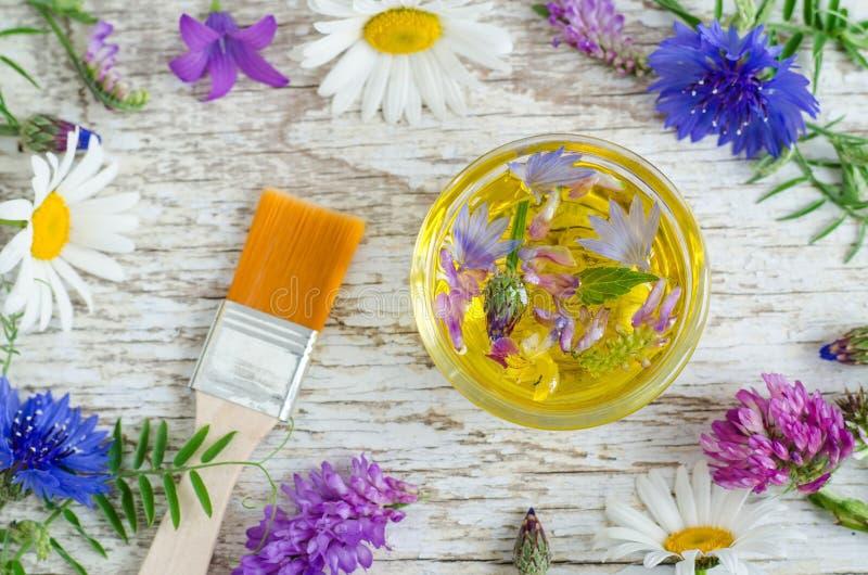 Petit bol en verre avec de l'huile cosmétique d'arome avec des extraits de fleurs Ingrédients de cosmétique naturel photographie stock libre de droits